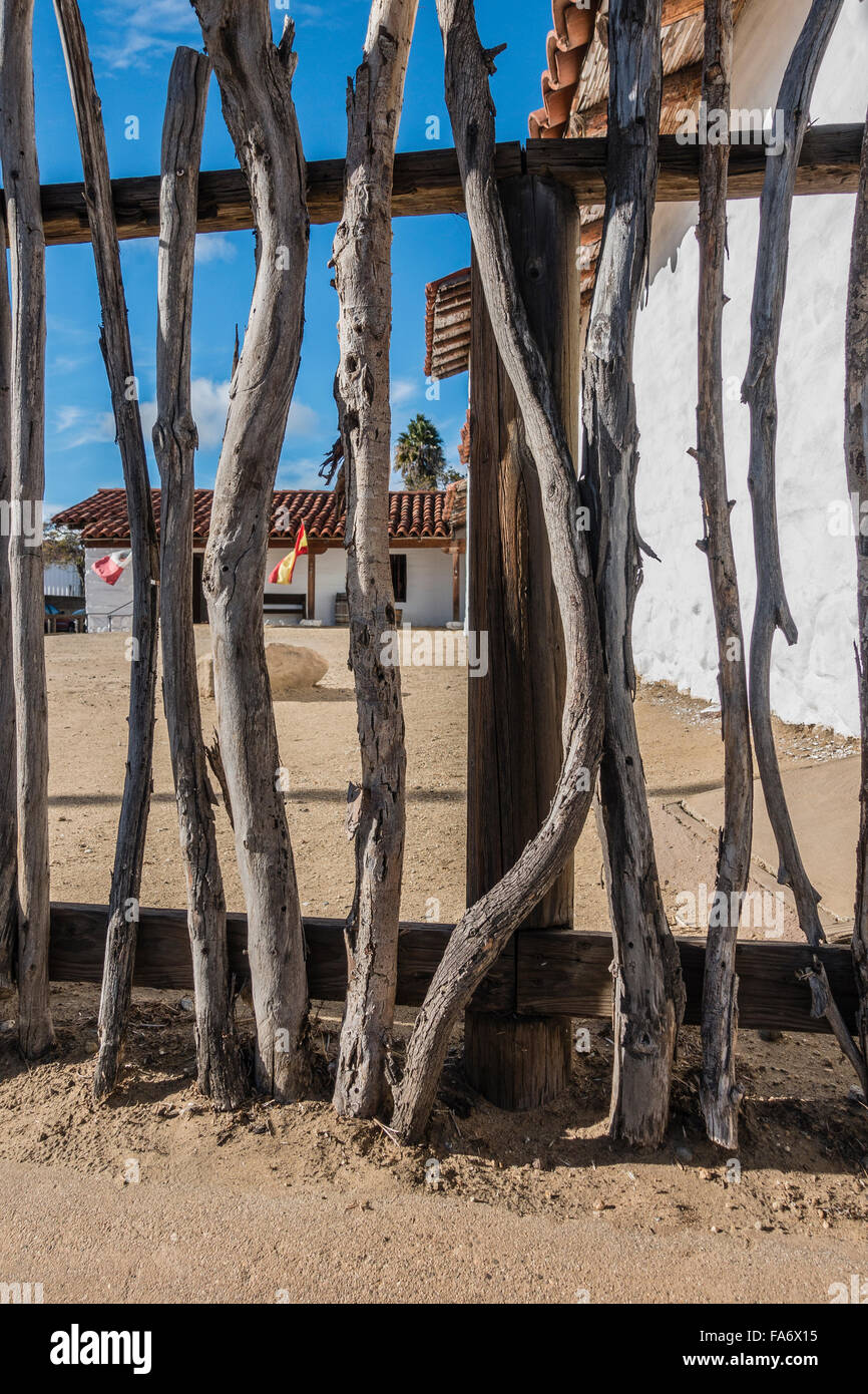 A primitive style fence made out of tree branches in the foreground at the Santa Barbara Presidio. - Stock Image