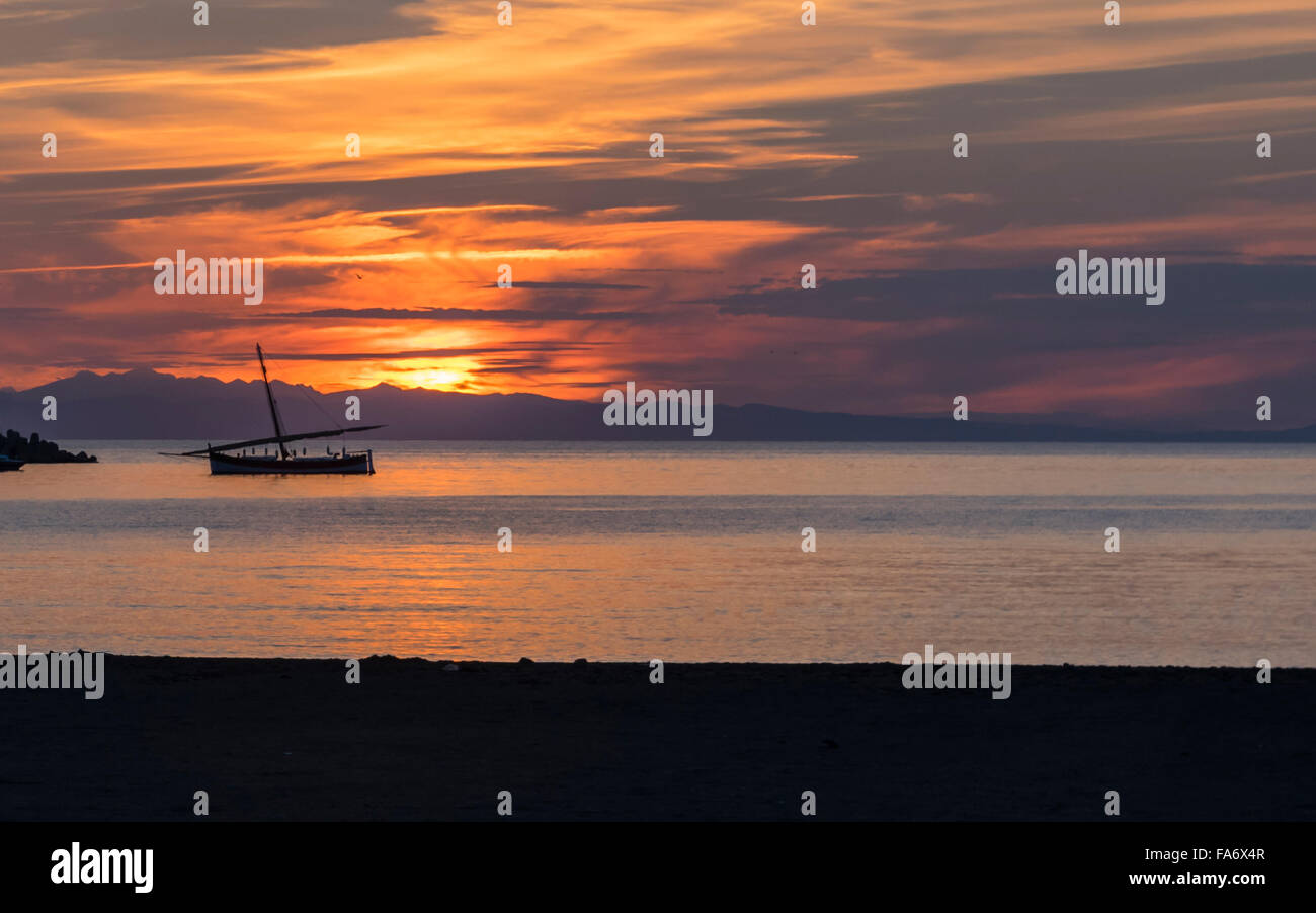 Sunset in Sestri Levante, Liguria, Italy. Bright cloudy orange sky and sea with dark anchored sail boat. - Stock Image