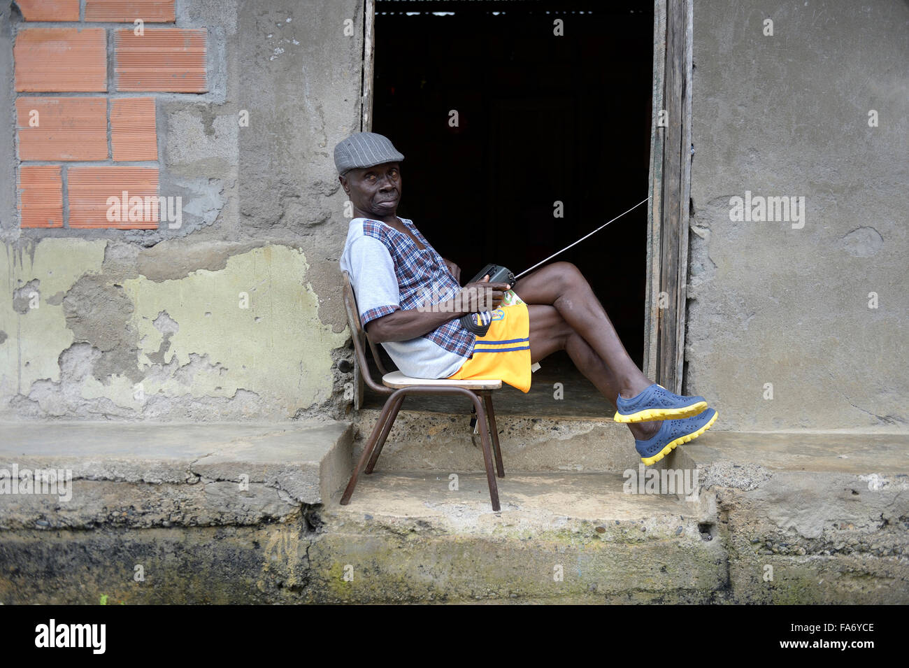 Man sitting with radio at the door, afro-columbian village of El Salto on the River Rio Andagueda, Chocó Department, - Stock Image