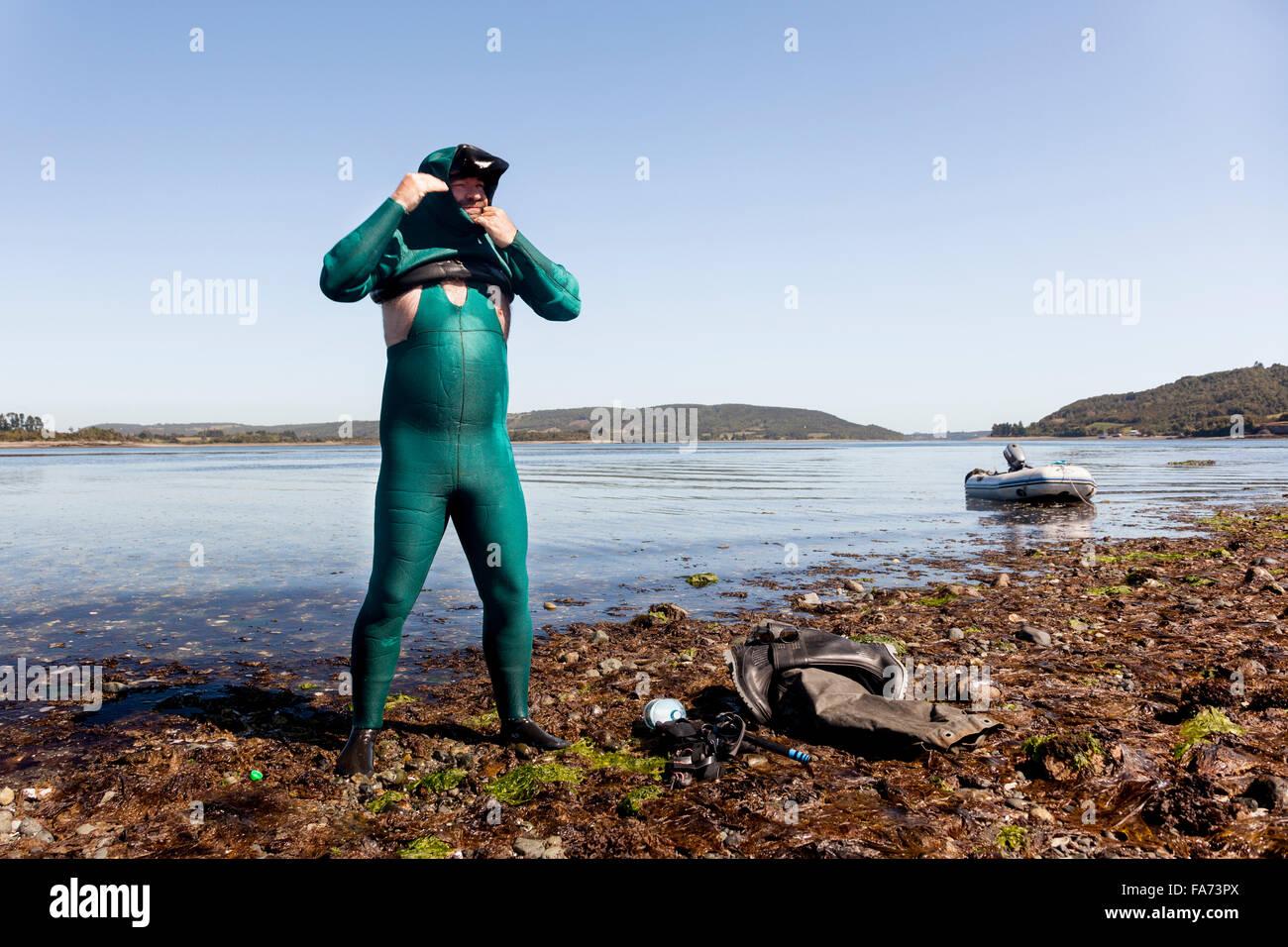 Carlos Lonza, a Chilean tourism entrepreneur, scientist and sailor prepares to dive for mussels near Chiloé - Stock Image