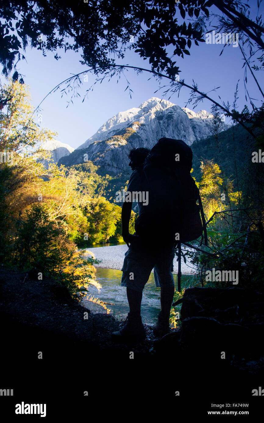 A hiker takes in the view of Mt Trinidad over the river in Chile's remote Cochamó valley - accessible only - Stock Image