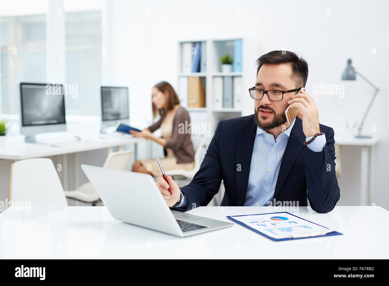 Confident businessman calling and looking at laptop display - Stock Image