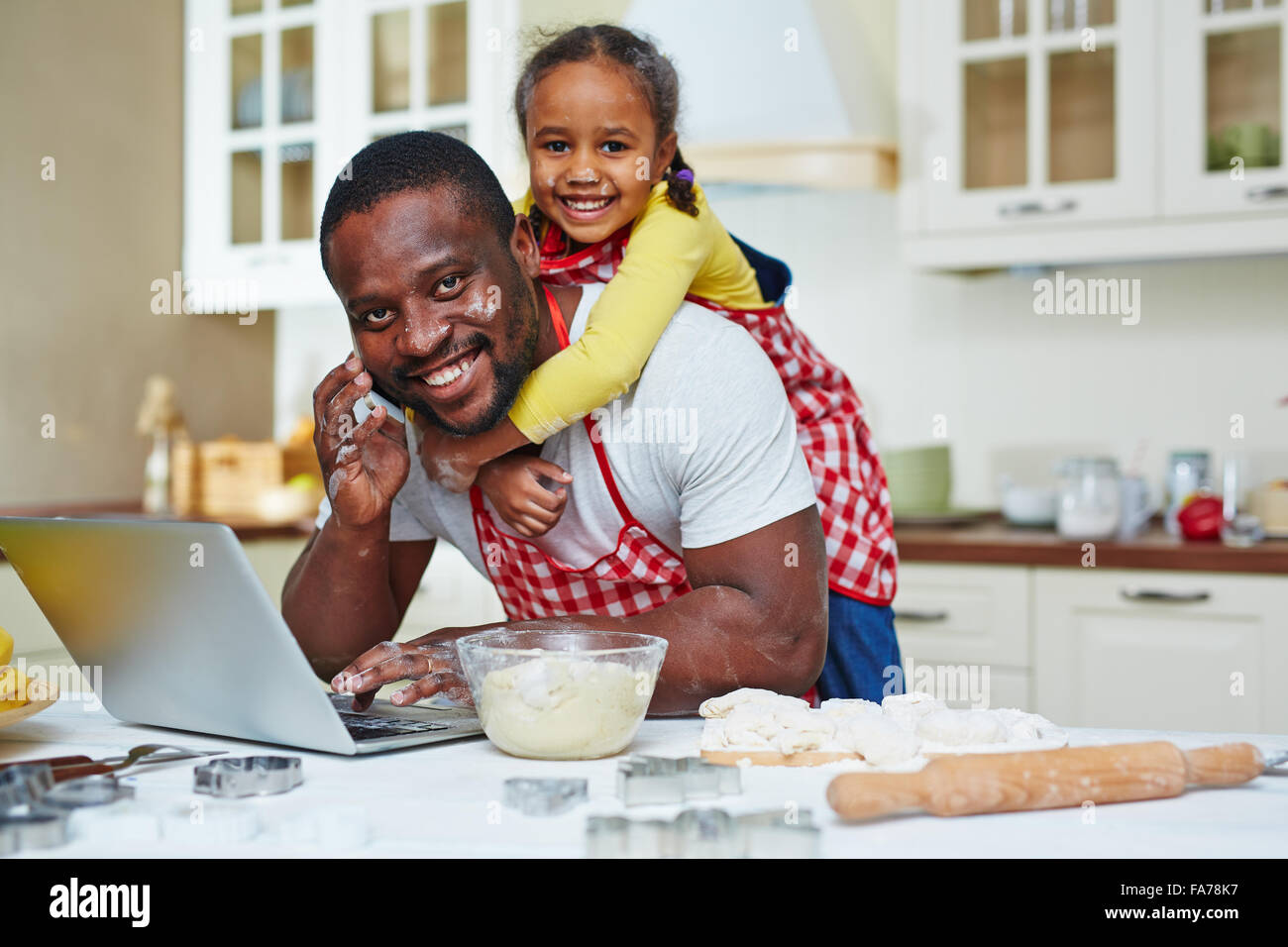 Busy father networking and speaking on cellphone with cute daughter on his back - Stock Image