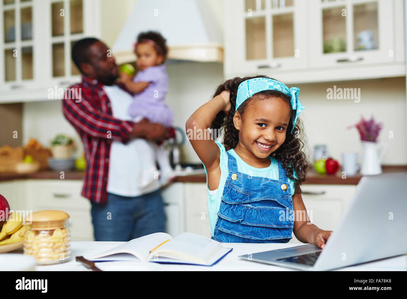 Happy African-American girl looking at camera while networking in the kitchen - Stock Image
