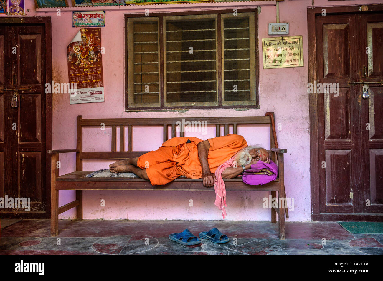 Old sadhu baba (holy man) sleeping on a bench - Stock Image