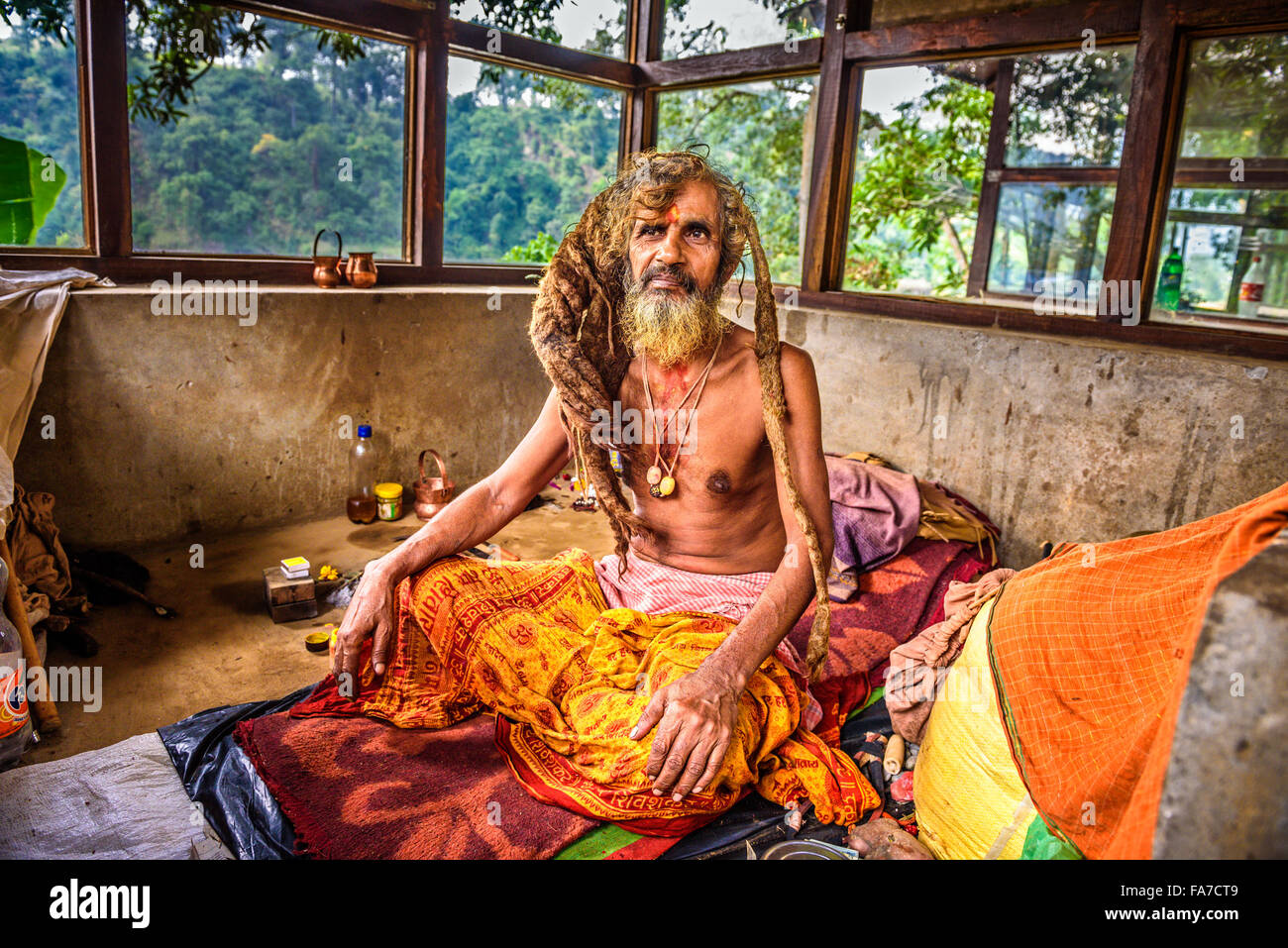 Sadhu baba  (holy man) with traditional long hair meditates in a temple - Stock Image