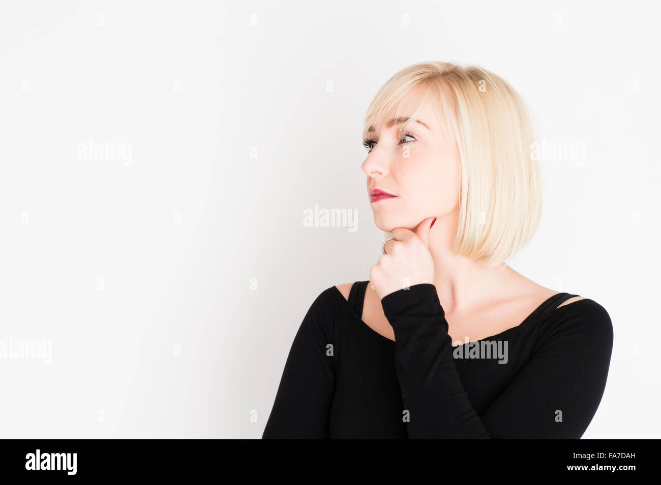Decision making - difficult life choices and options : A young slim blonde blond haired woman girl, thinking, pondering, - Stock Image