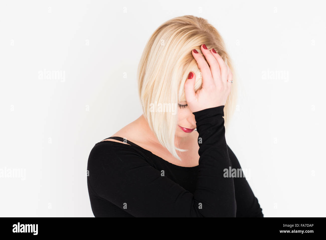 A young slim blonde blond haired woman girl, sad upset unhappy distraught grieving bereft depressed UK - Stock Image