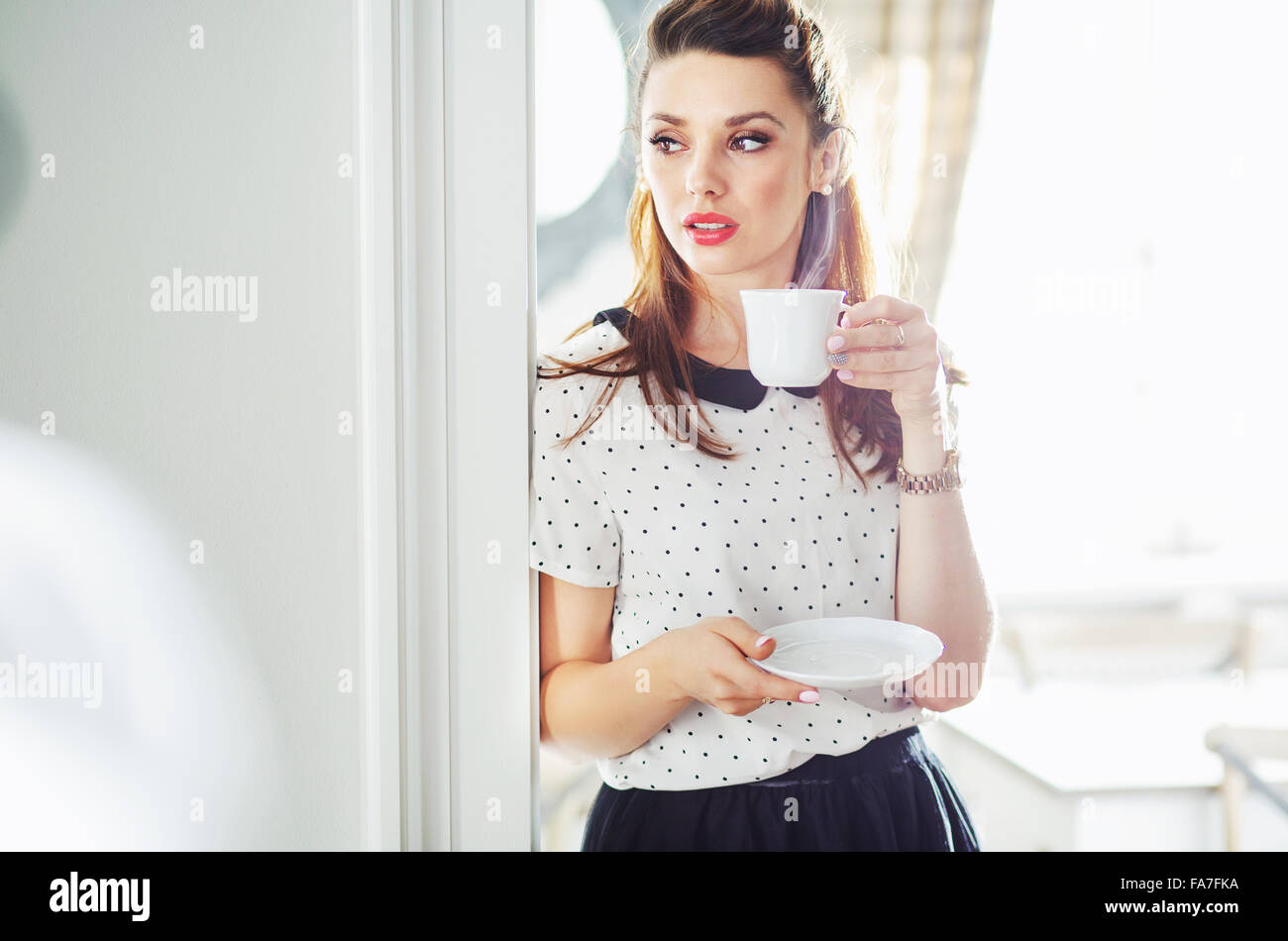 Adorable young woman drinking tasty coffee - Stock Image