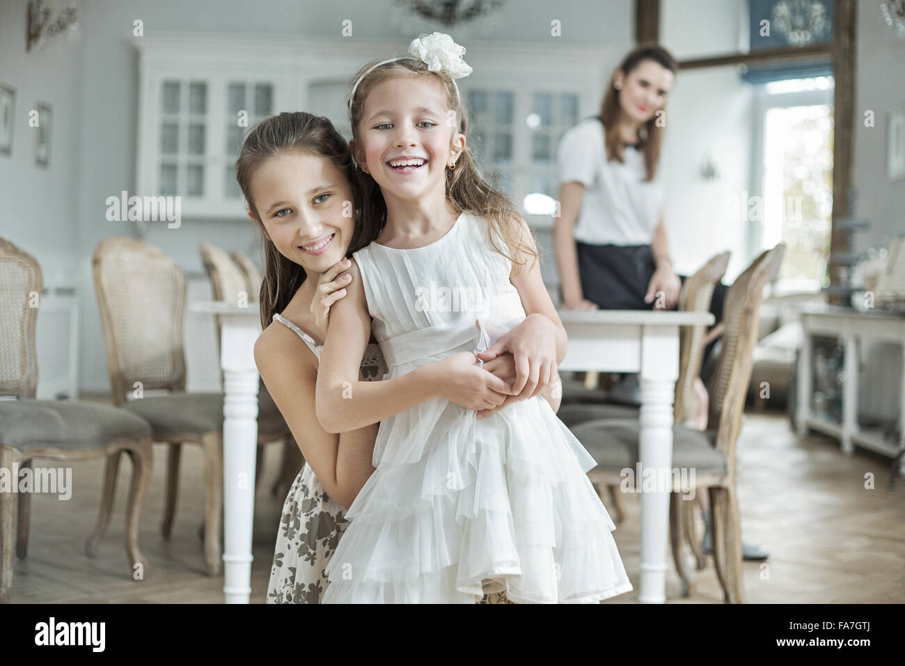 Two cheerful daughters posing with pretty mother - Stock Image