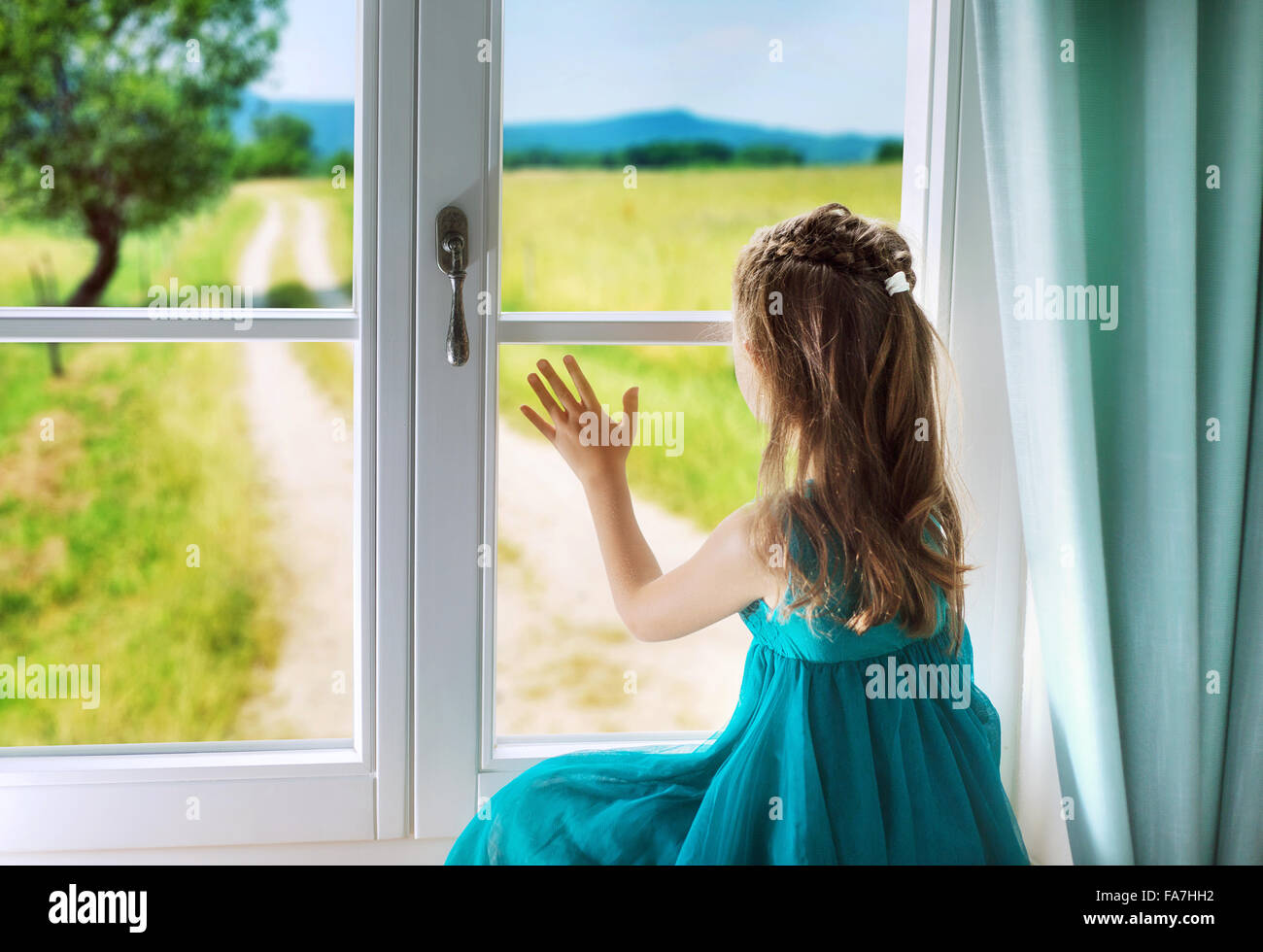 Little sad girl looking through window