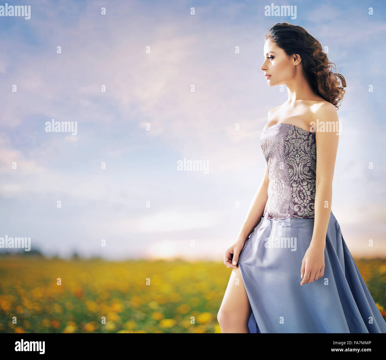 Pretty woman on the summer wheat field - Stock Image