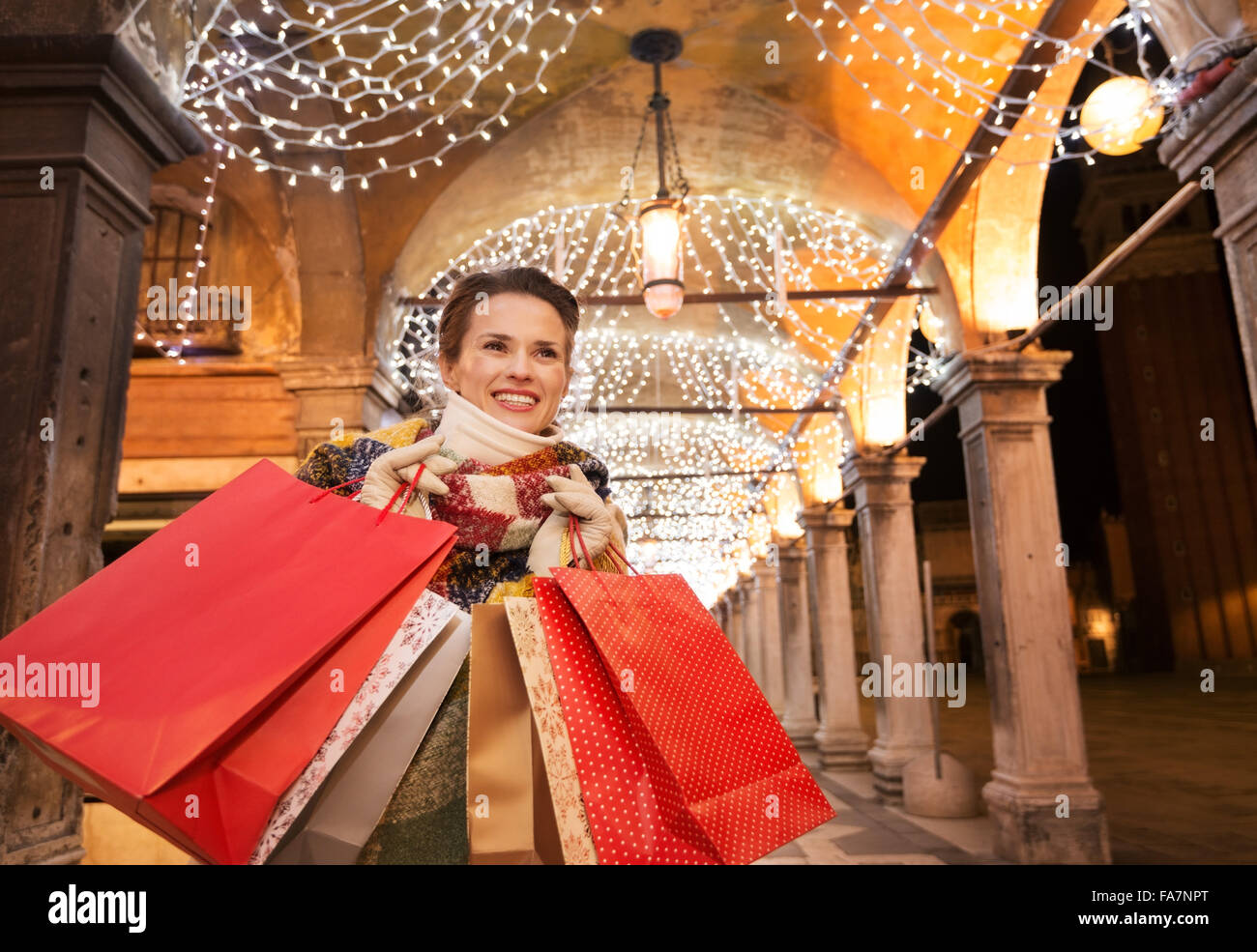 It is time for fashion forward shopping for a most desirable Christmas gifts in Venice, Italy. Happy woman with - Stock Image
