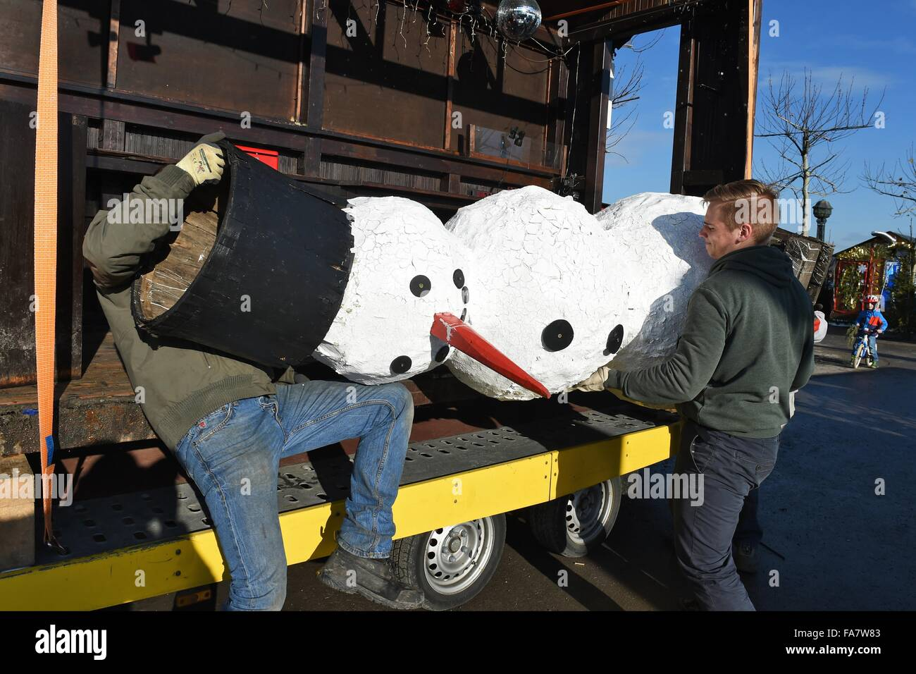 People lift a cardbpard snowman onto a trailer beside lake Constance ...