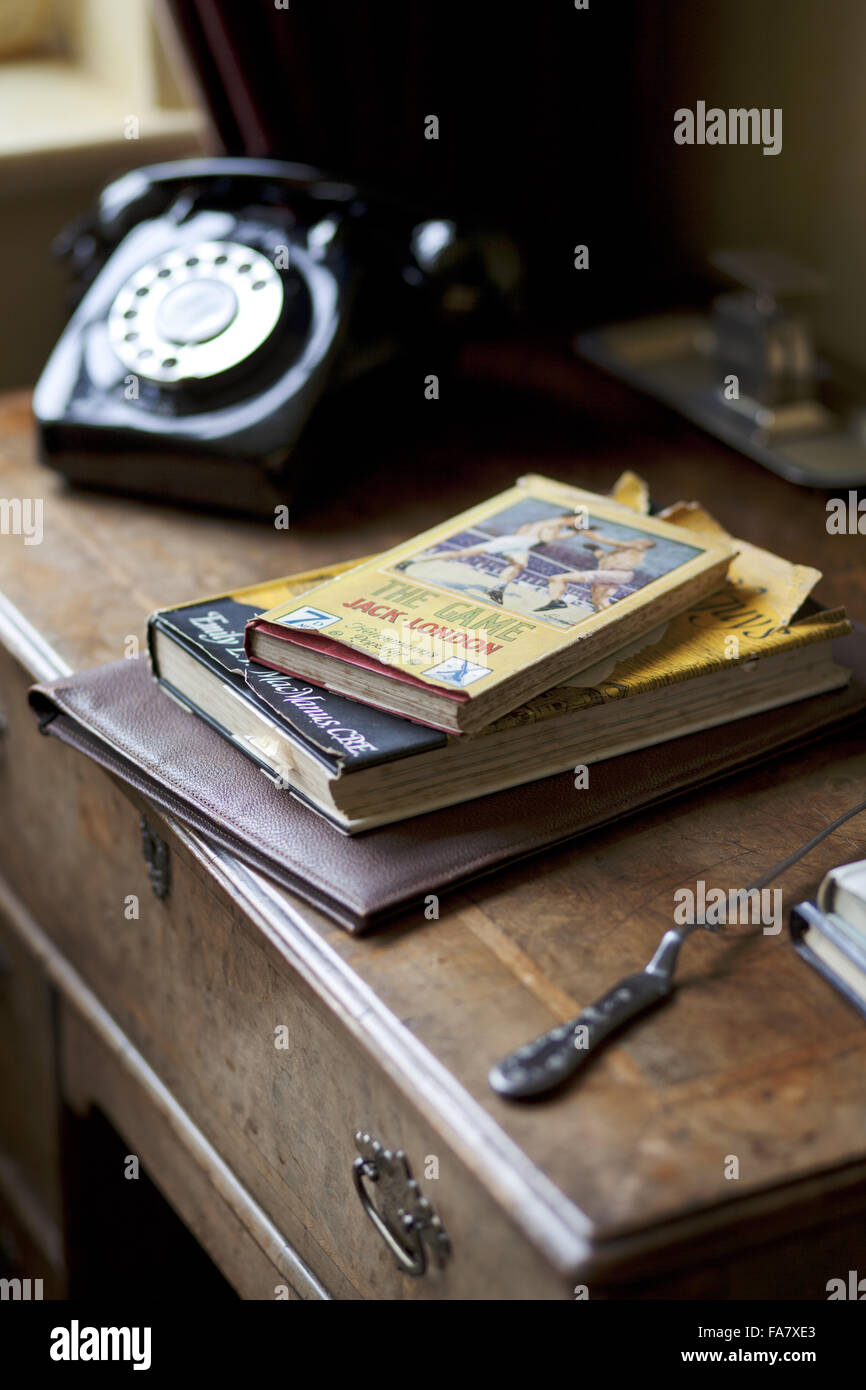 Detail of a desk with books, a letter-opener and telephone, in the sitting room/study, Nuffield Place, Oxfordshire. - Stock Image