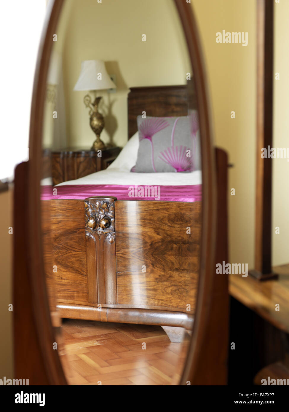 Detail of a bed and lamp in Geoffrey Bushby's bedroom, seen reflected in an oval mirror, Portland House, Dorset. - Stock Image