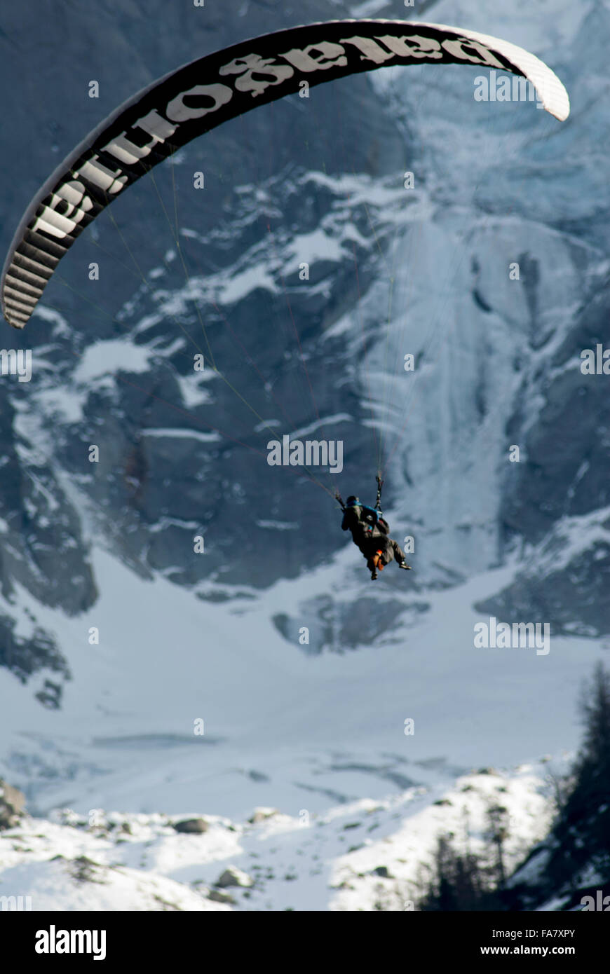 Tandem paraglider pilot flying his wing with passenger in front of glacier - Stock Image