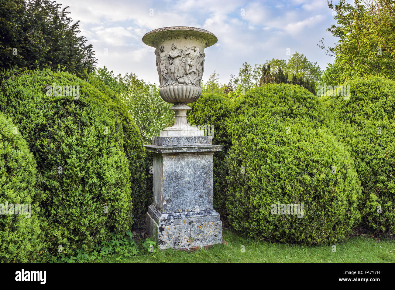 The neatly trimmed hedges and a stone urn in the gardens at Uppark House and Garden, West Sussex - Stock Image