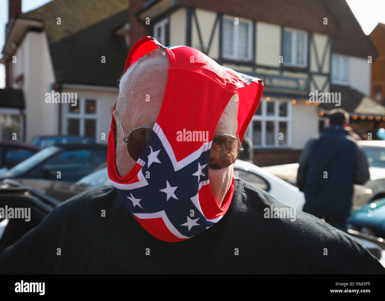 A man with knickers on his head that feature a confederate style flag design. - Stock Image