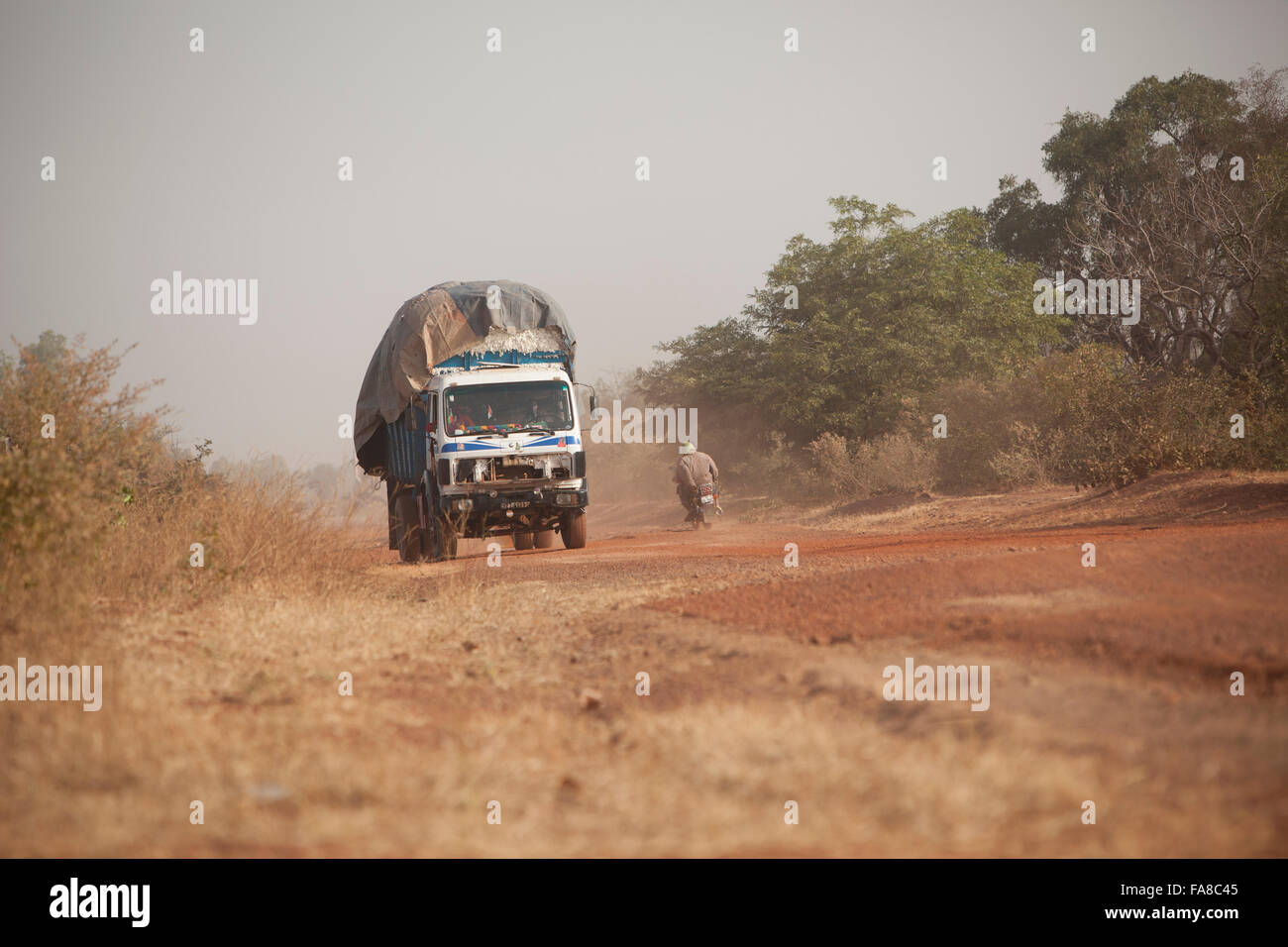 An overloaded truck travels down a dusty road in Kouka Department, Burkina Faso. - Stock Image