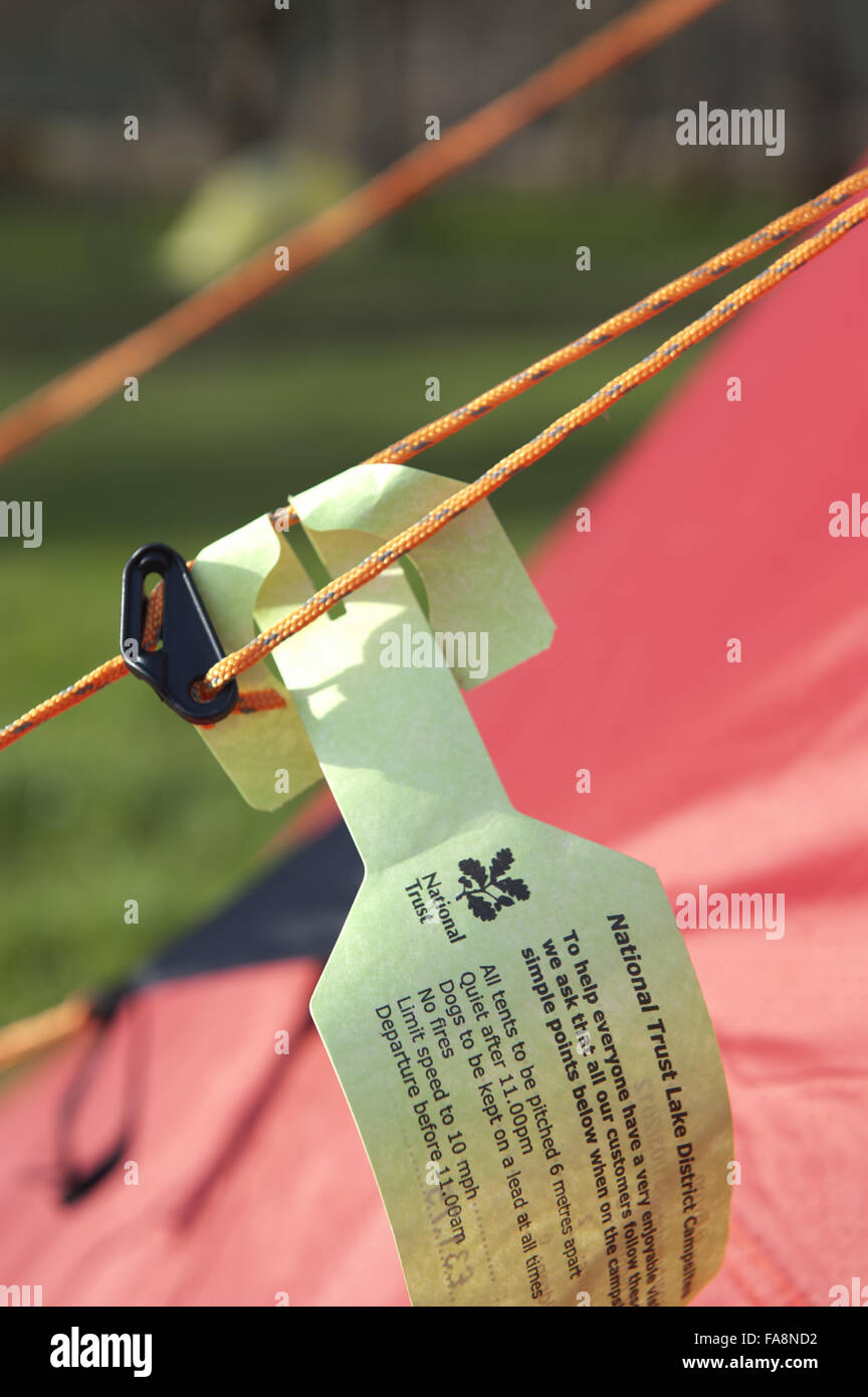 Regulations on a ticket attached to the guyropes at the National Trust campsite at Wasdale, Cumbria. - Stock Image