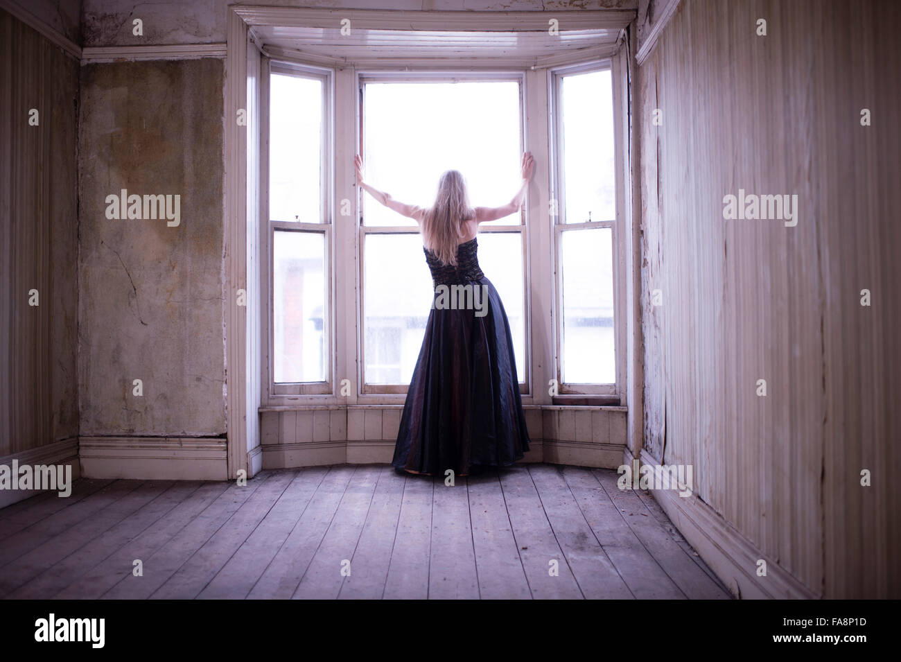 a young slim blonde haired woman wearing a long ball gown dress alone in a rundown derelict room building standing - Stock Image