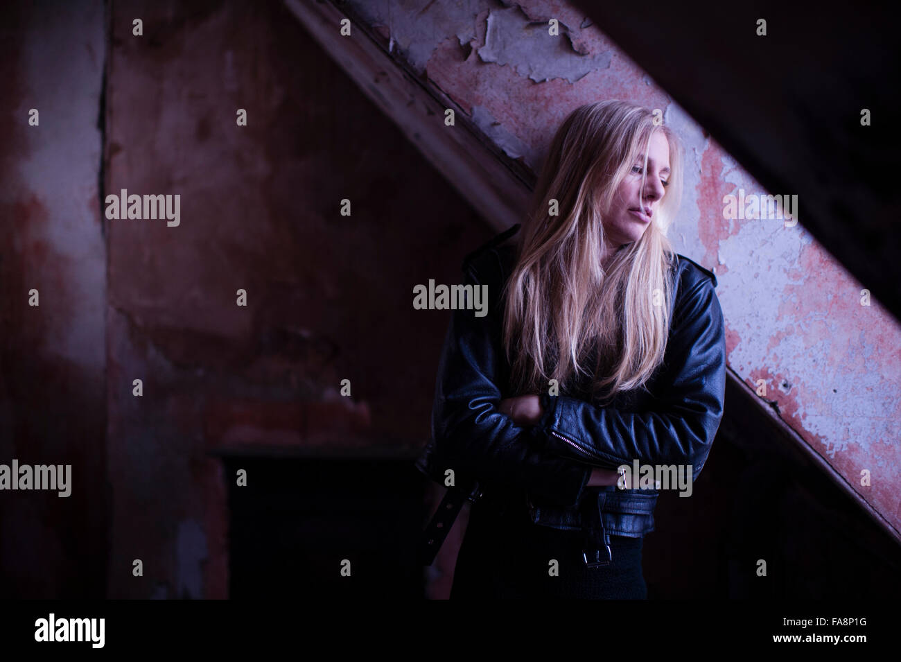 A sad lonely depressed young slim blonde haired woman alone in a rundown derelict room building UK - Stock Image