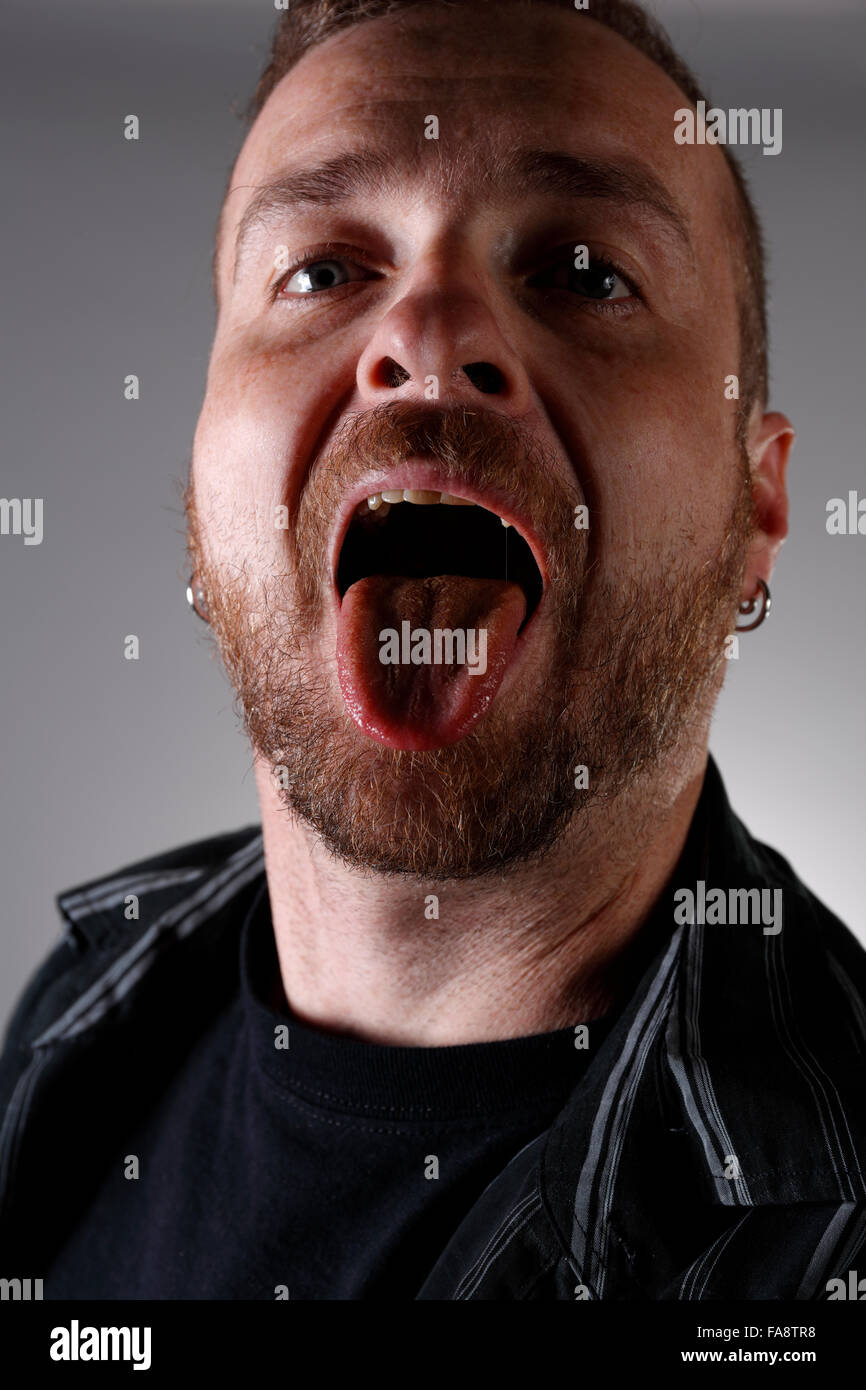 Man with open mouth showing tongue. - Stock Image