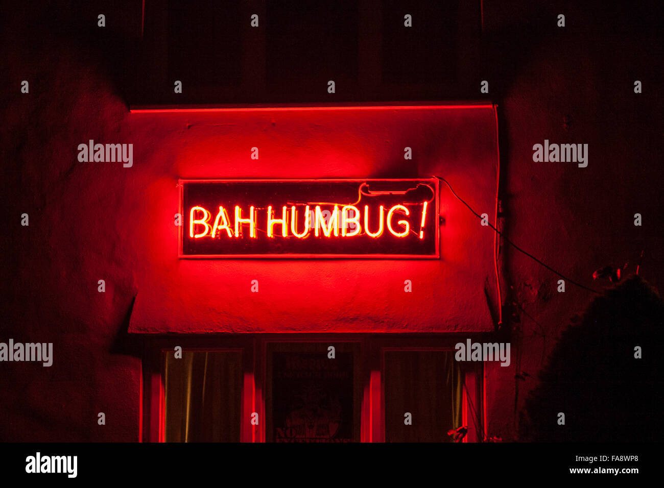 Neon Sign in Essex cottage window at christmas  Bah Humbug!   A non festive spirit Christmas neon sign outside  - Stock Image