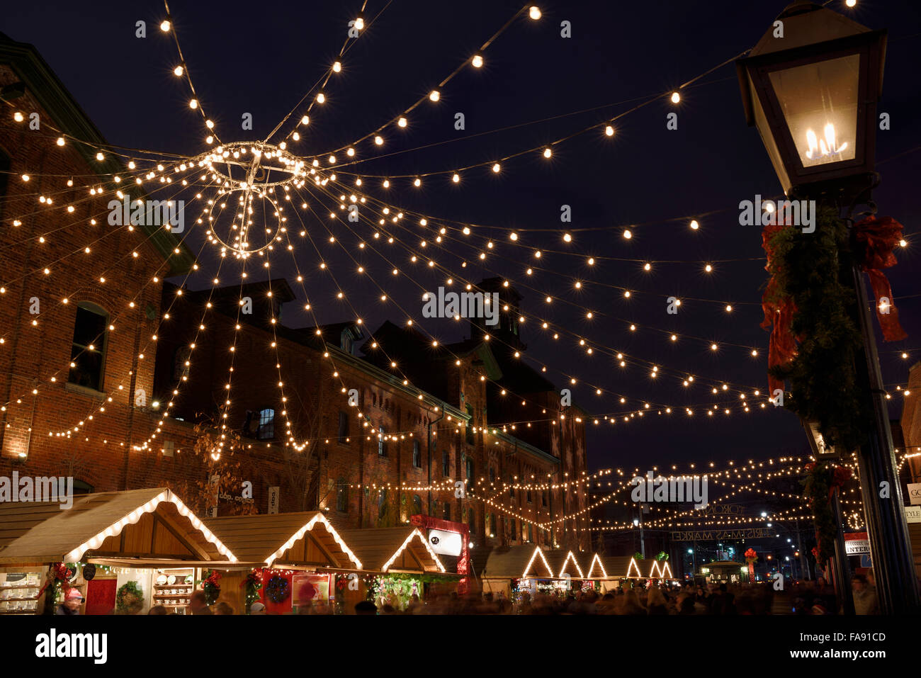 Lights strung over Trinity Street historic Distillery District for the Toronto Christmas Market with gas lamp at Stock Photo