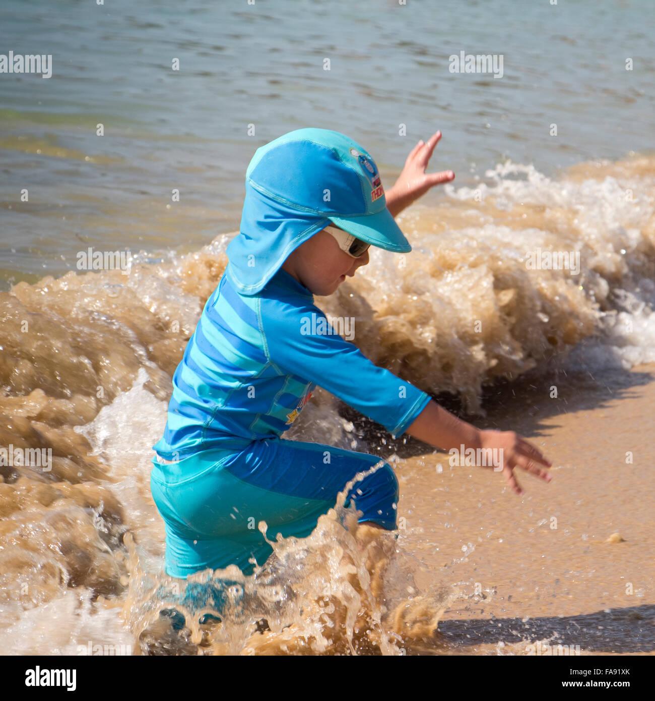 Boy playing on the beach at Praia De Santa Eulalia, near Albufeira, Algarve, Portugal Stock Photo