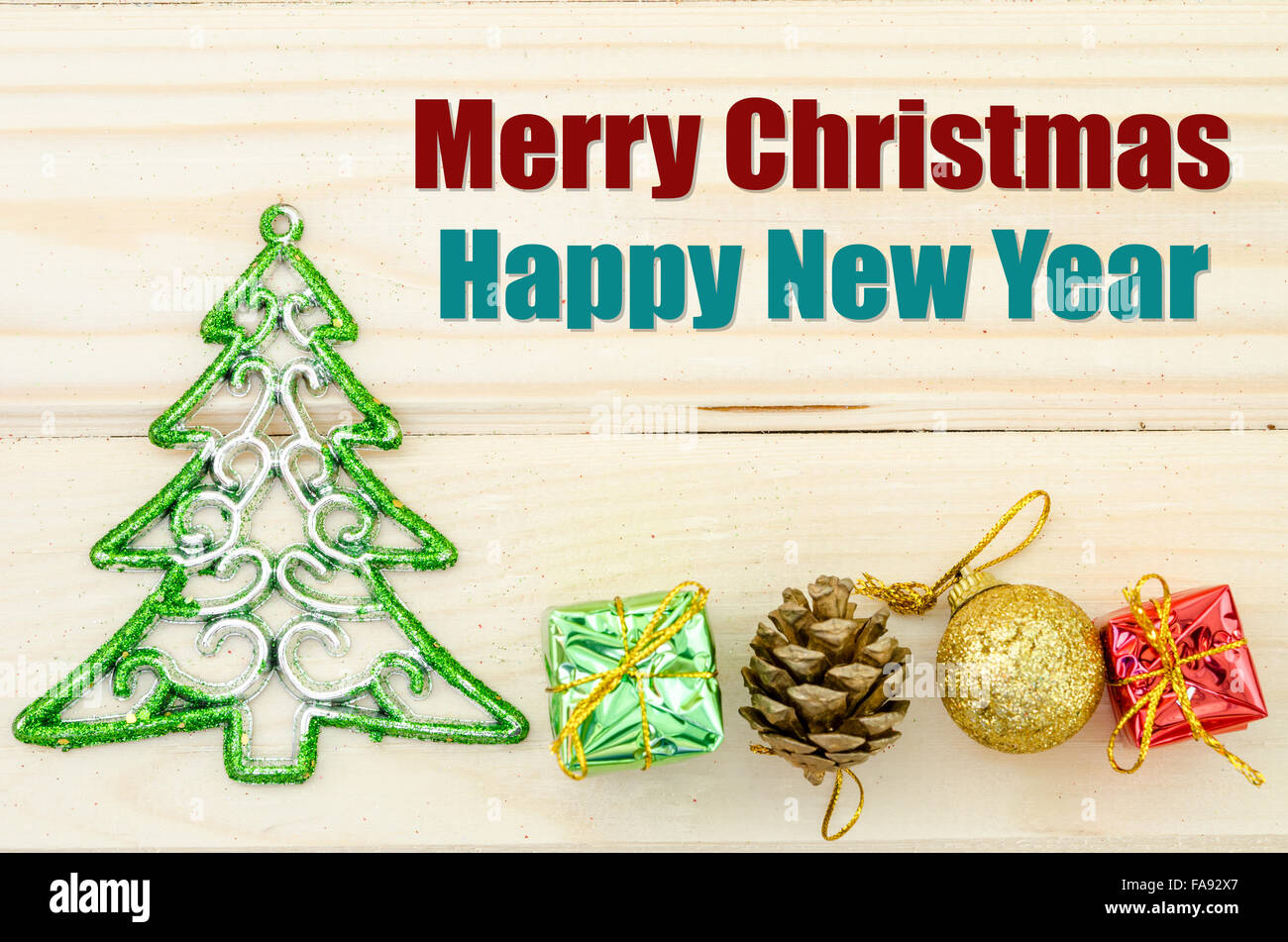 Merry Christmas and happy new year wording with christmas decorations on wooden background. - Stock Image