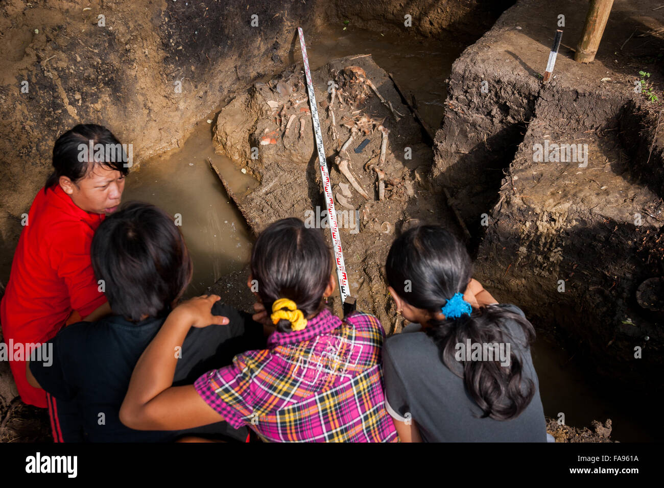 Local people discuss while visiting an archaeological excavation site of prehistoric human skeletons in Cikuntul, - Stock Image