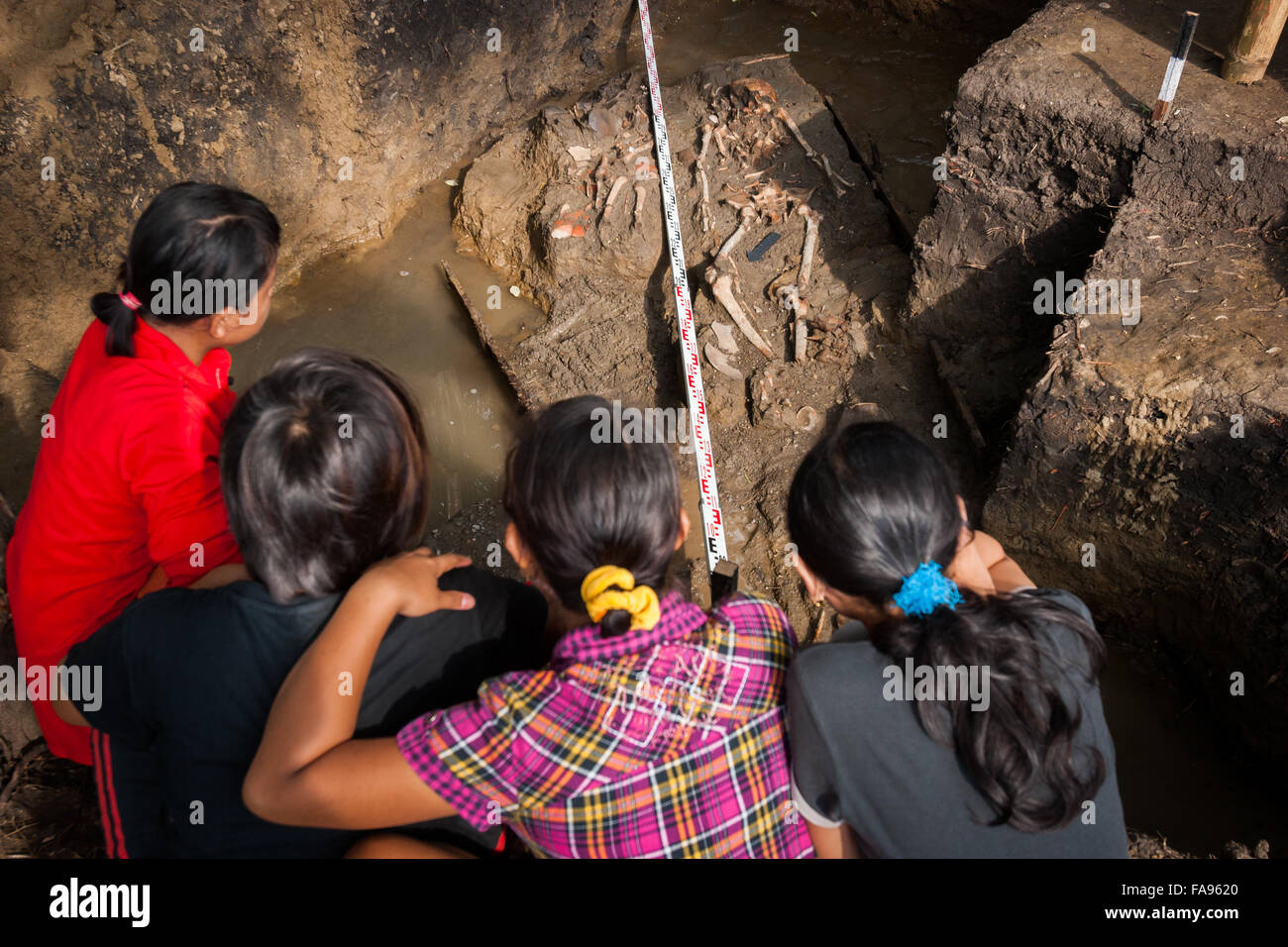 Local people watching archaeological excavation site of prehistoric human bones. - Stock Image