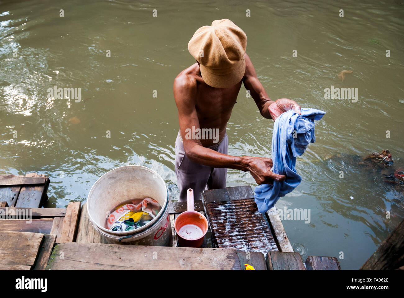 Man washing clothes on Ciliwung riverbank, Jakarta. Ciliwung is said as one of the most heavily polluted rivers - Stock Image