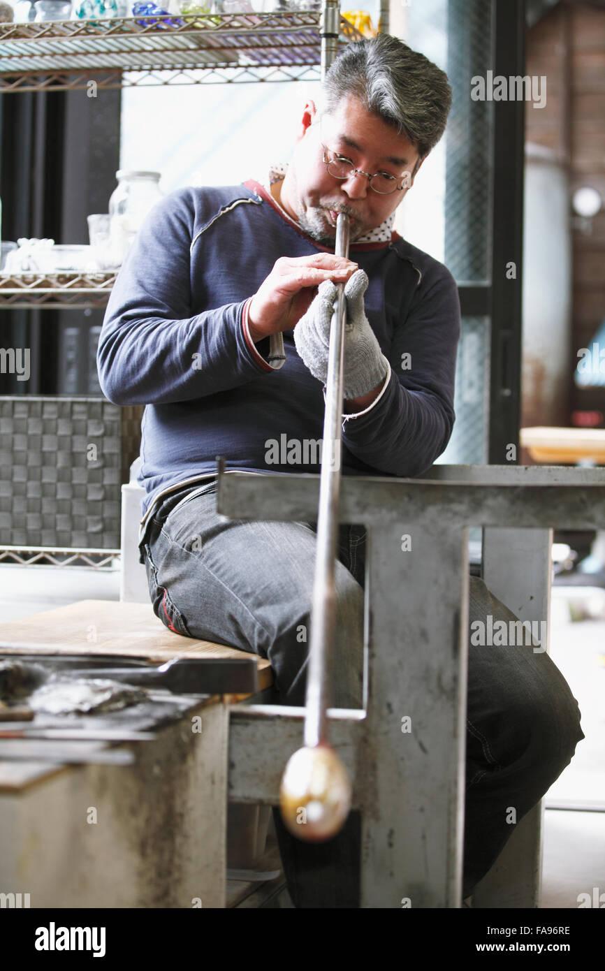Japanese glass artisan working in the studio - Stock Image