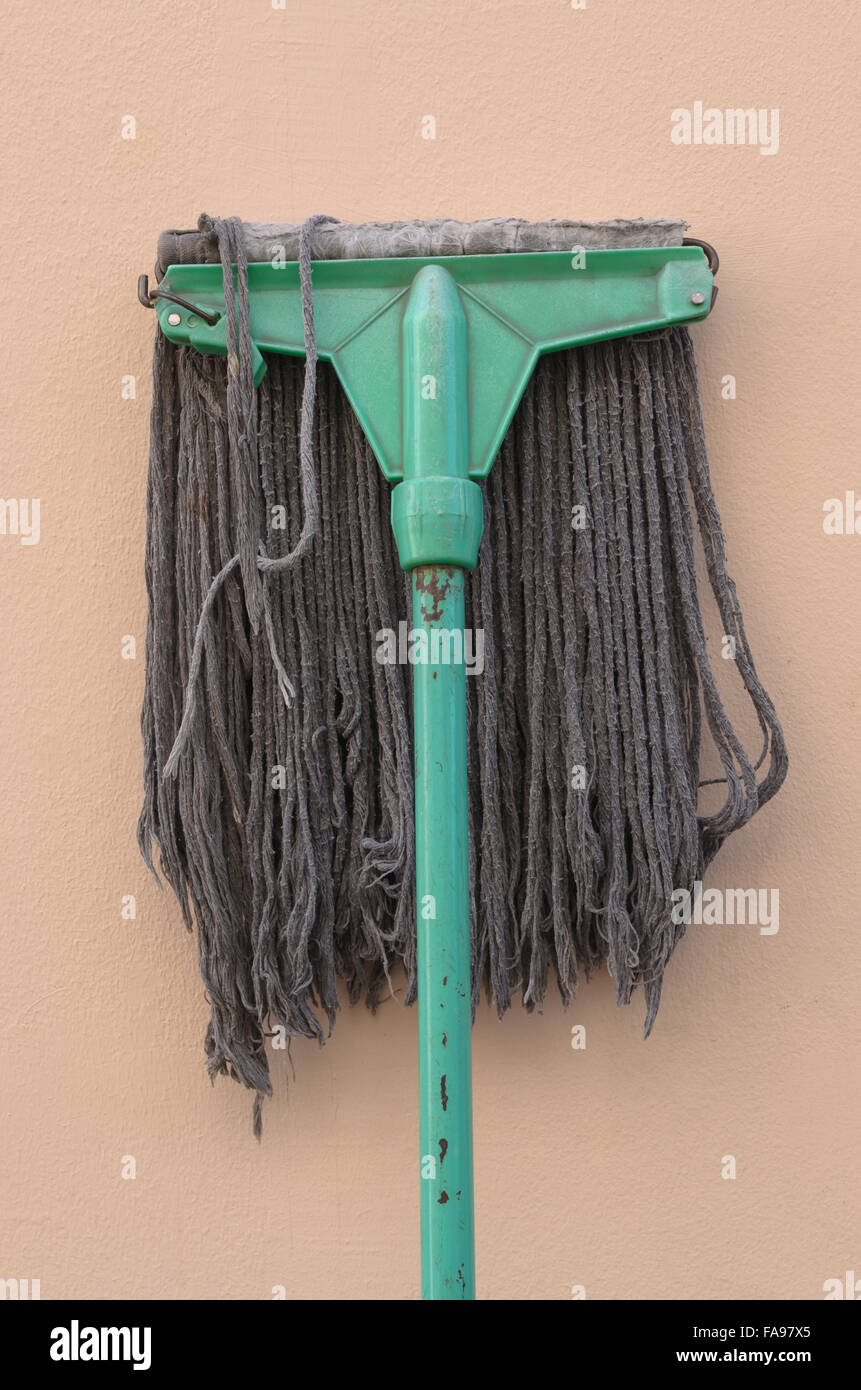 Old mop lying against a pink wall. - Stock Image