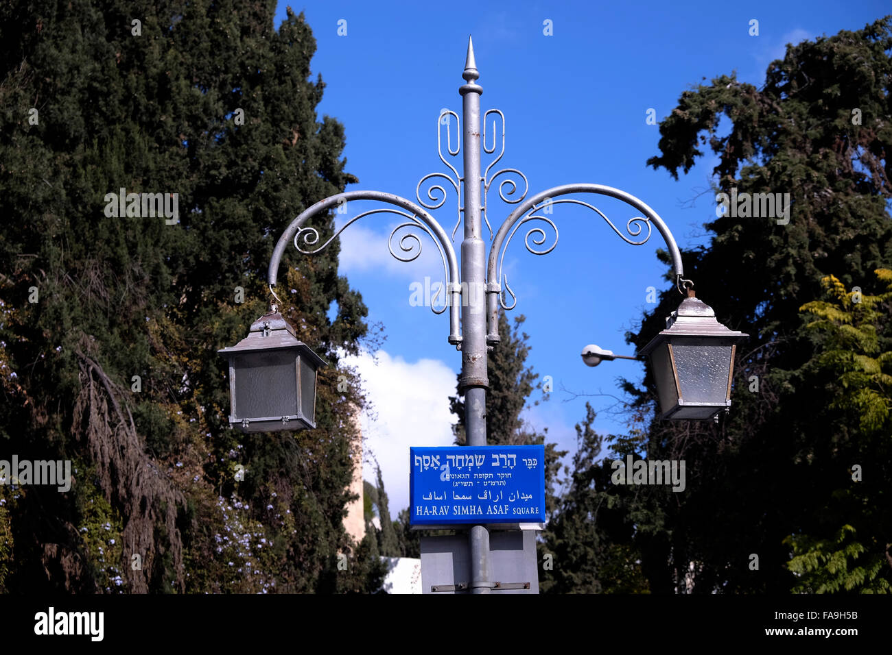 Street sign in Hebrew English and Arabic on old lamppost in Rehavia also Rechavia neighborhood in West Jerusalem - Stock Image