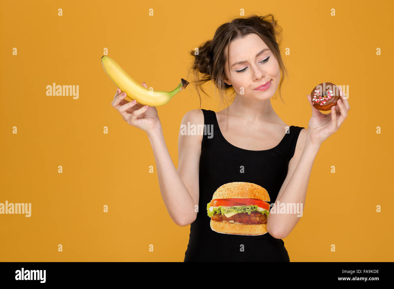Confused thoughtful cute young woman with banana and donut choosing between healthy and unhealthy food over yellow - Stock Photo
