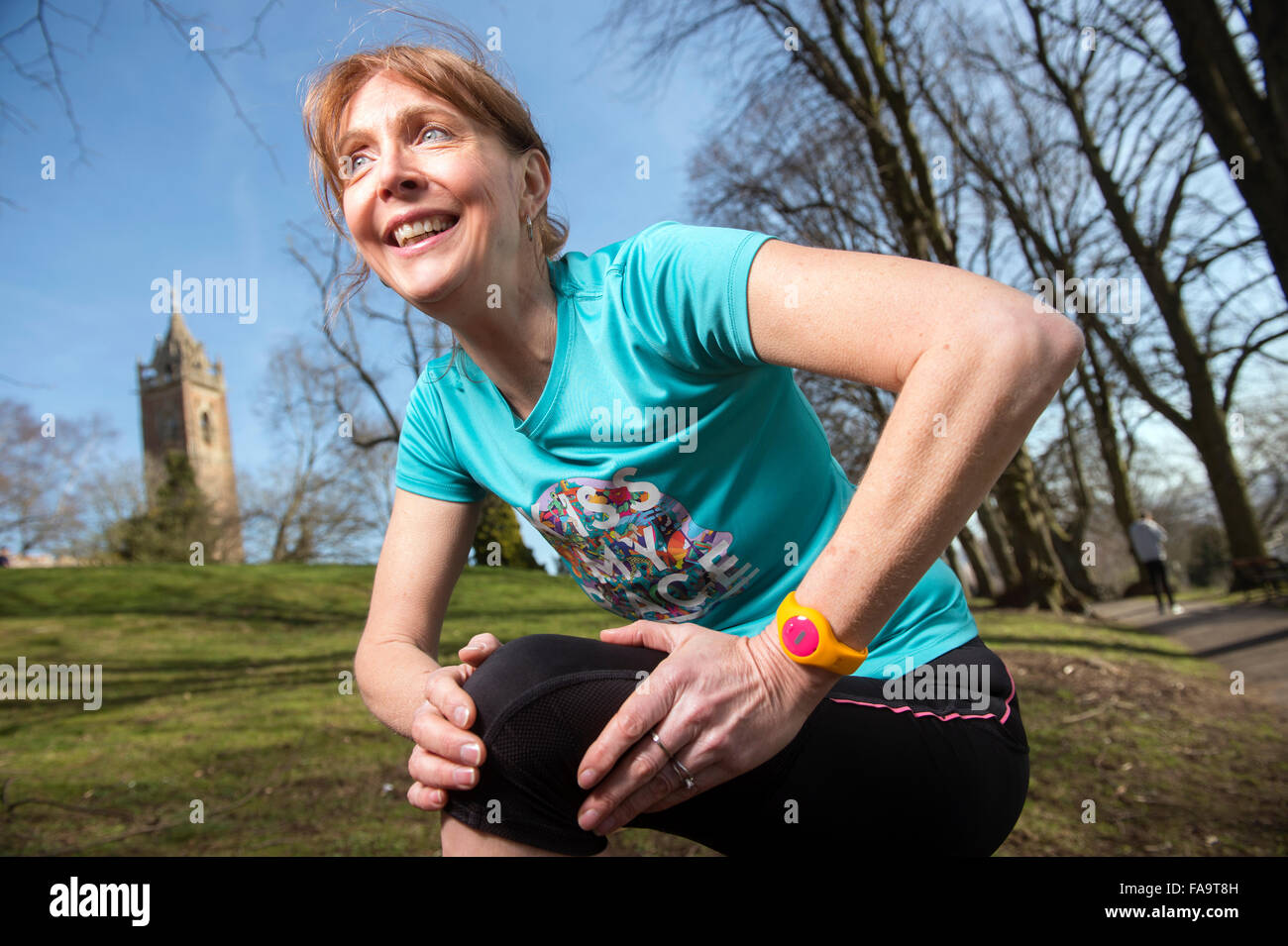 A female jogger wearing an activity tracker stretching before a run UK - Stock Image