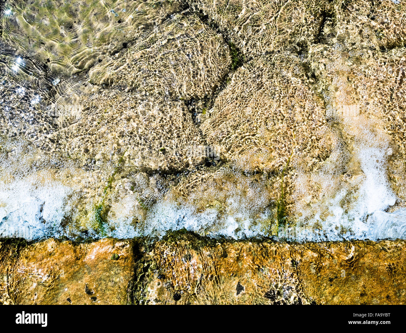 Background formed by the water of a stream flowing over rocks. - Stock Image