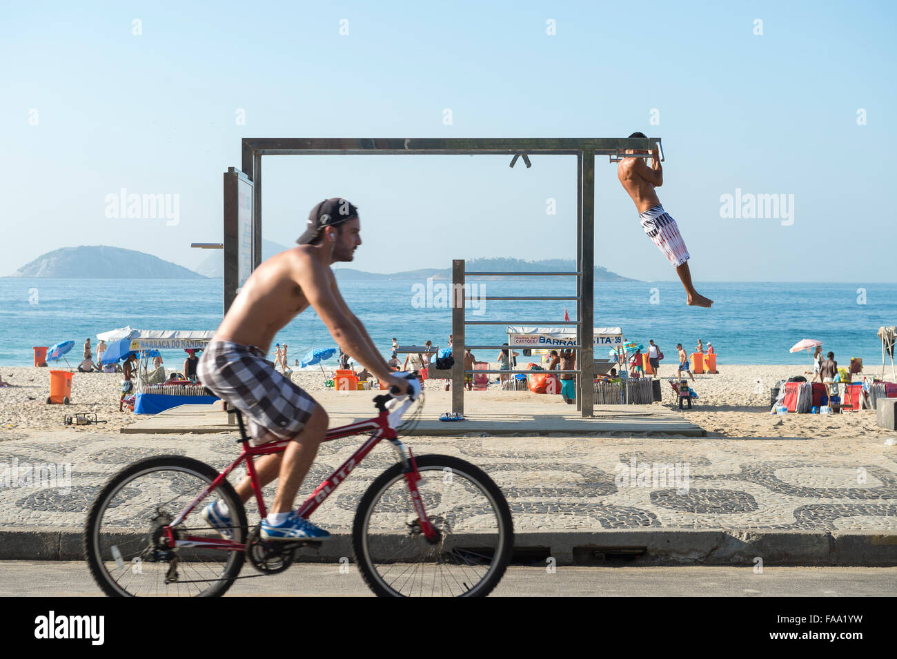RIO DE JANEIRO, BRAZIL - FEBRUARY 22, 2015: A cyclist passes a young man utilizing an outdoor fitness station in - Stock Image