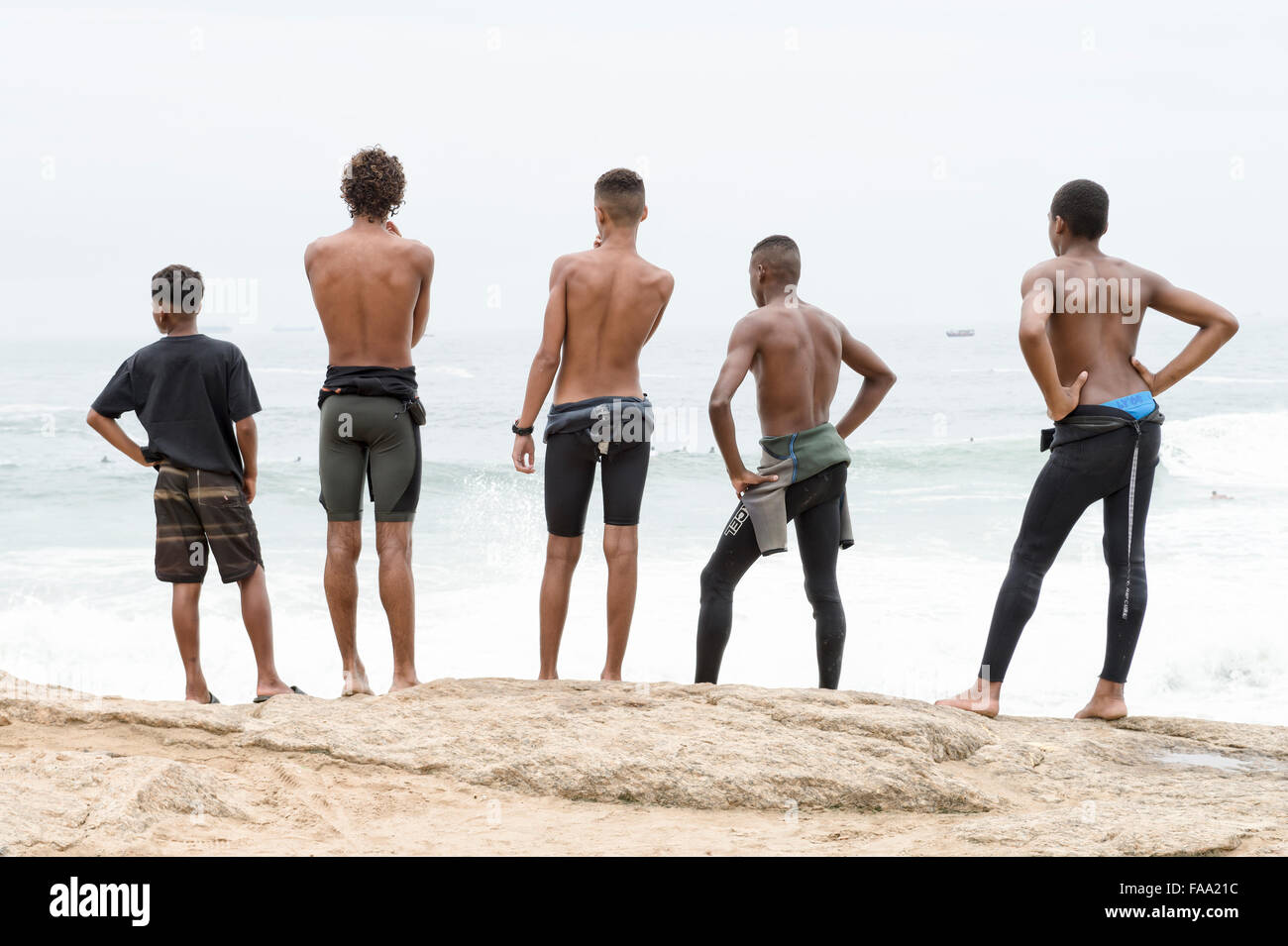 RIO DE JANEIRO, BRAZIL - OCTOBER 22, 2015: Brazilian surfers in wetsuits stand looking at incoming waves at Arpoador. - Stock Image