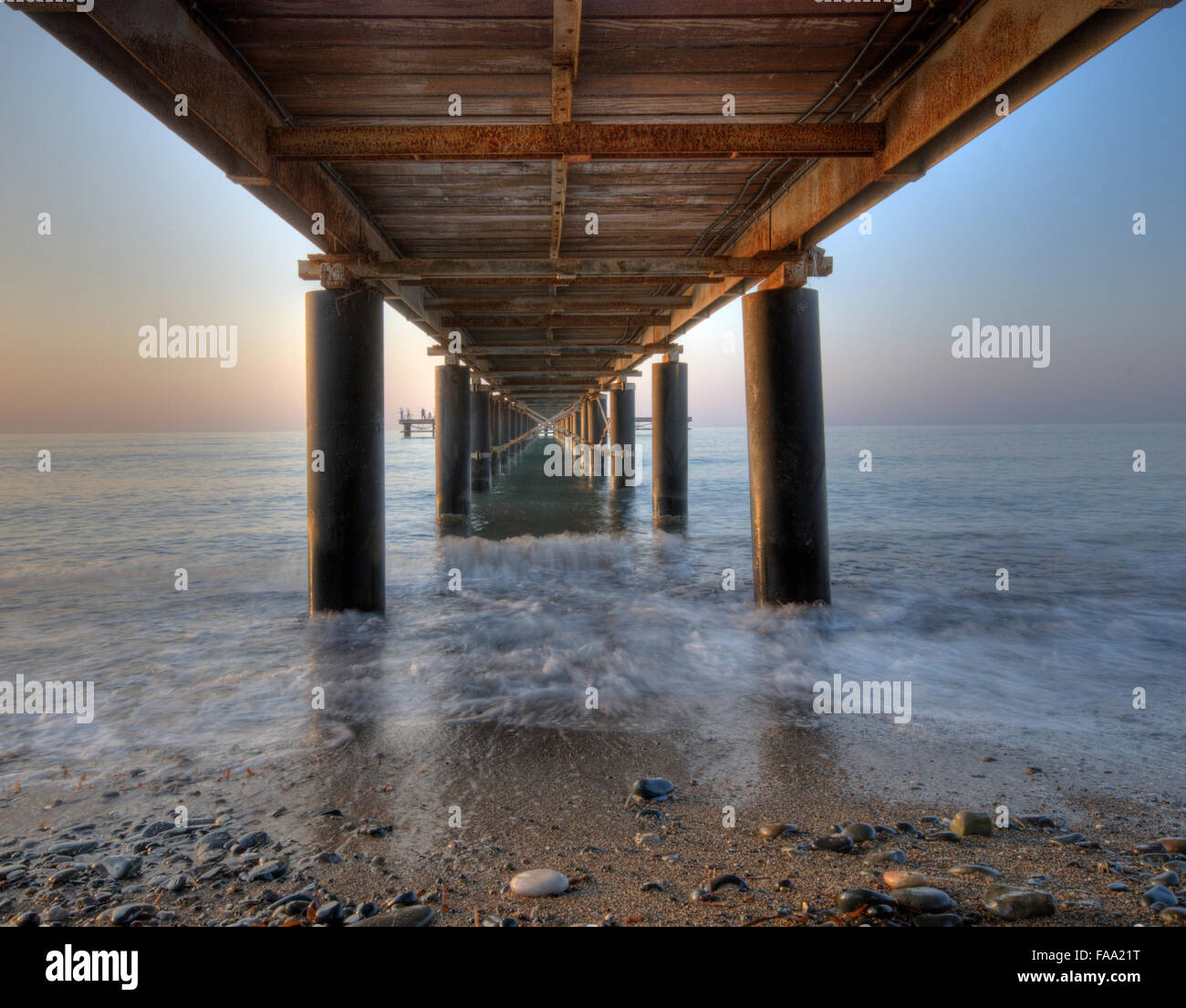 Rusty metallic  pier from sea level in horizontal composition creating a diagonal tunnel. - Stock Image