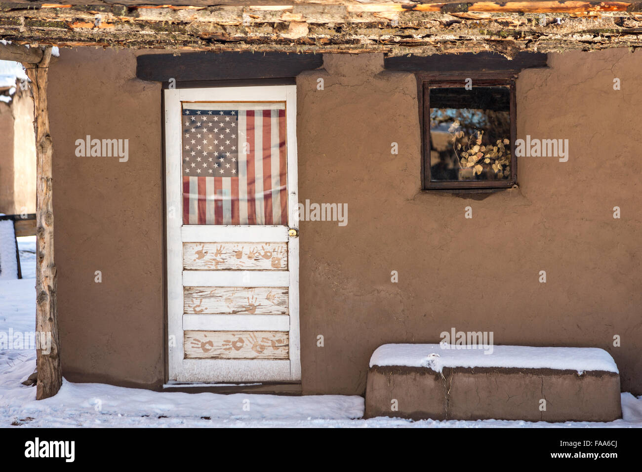 An American flag hangs from a door in an old adobe home at the ancient Native American Taos Pueblo outside Taos New Mexico. The pueblos are considered to ... & An American flag hangs from a door in an old adobe home at the Stock ...