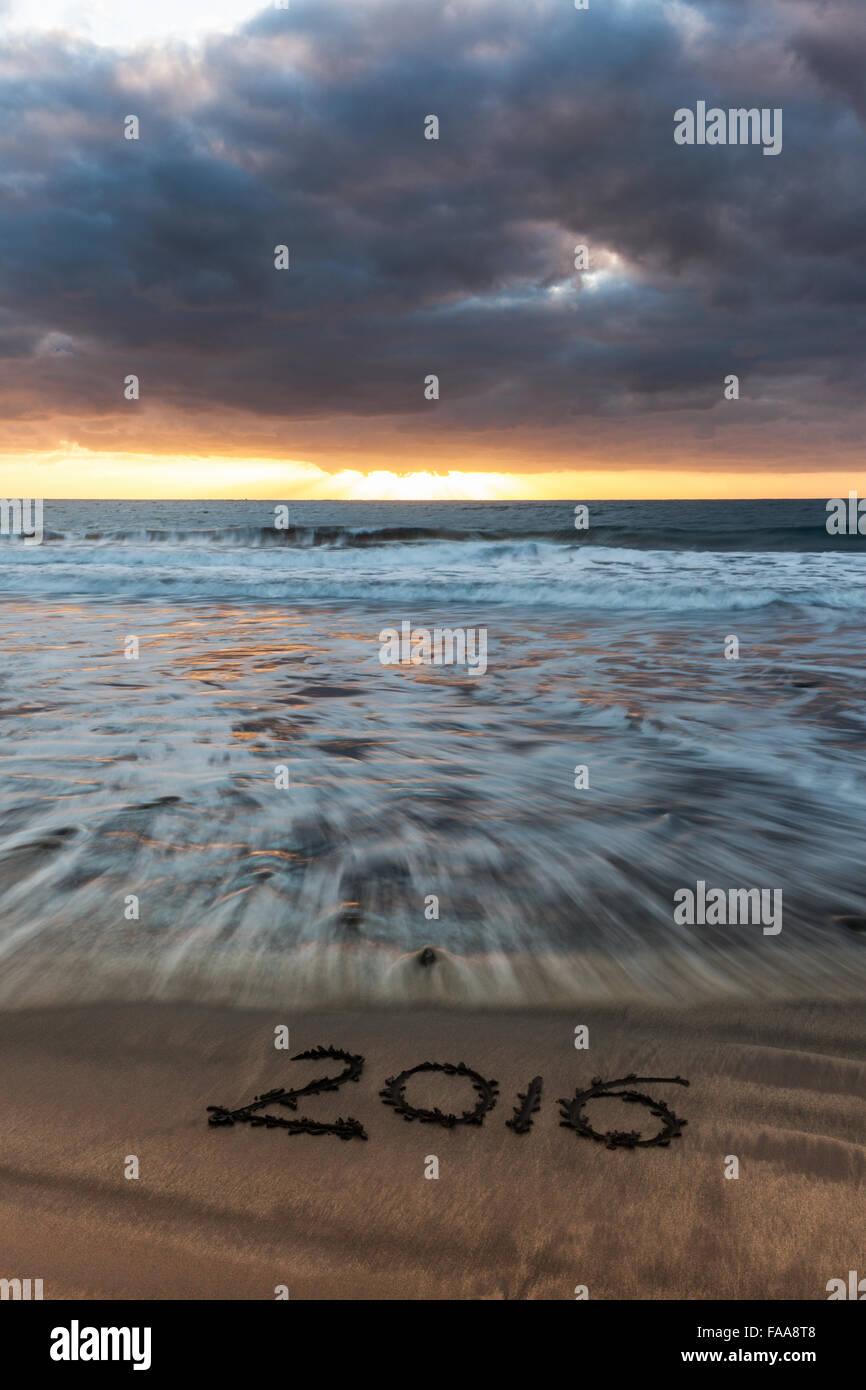 2016 - written on the beach at sunrise - Stock Image