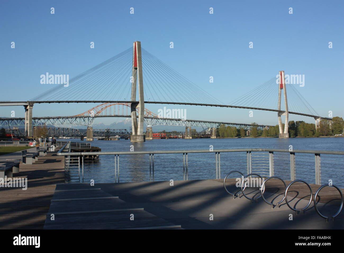 The Skytrain Bridge over the Fraser River in New Westminster seen from  Westminster Pier Park - Stock Image