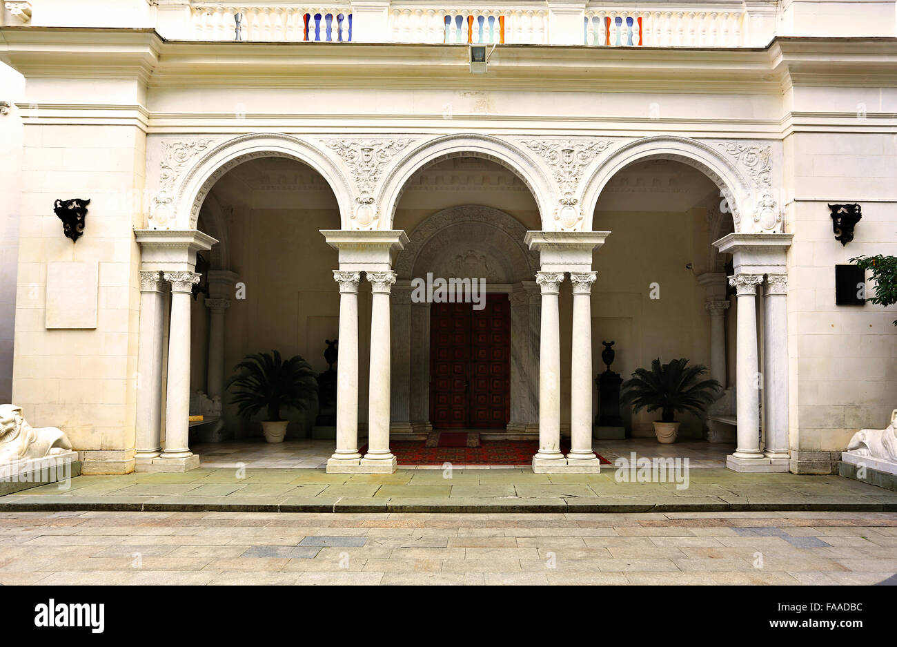 Main entrance in a white classical  palace with arches and columns - Stock Image