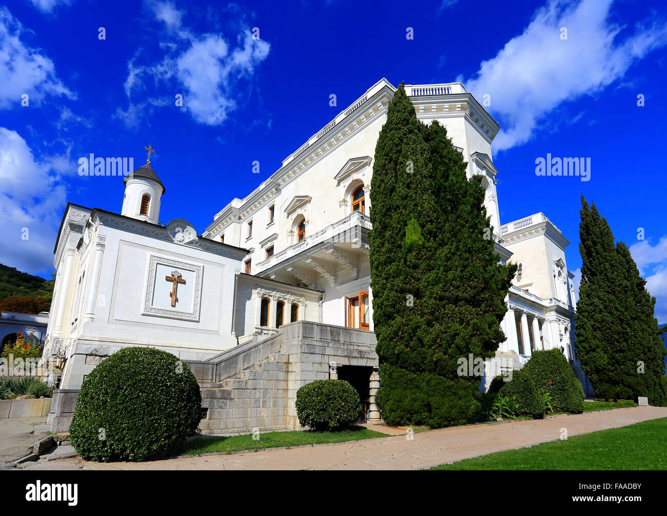 White Palace within subtropical cypress trees, pines and palm trees - Stock Image