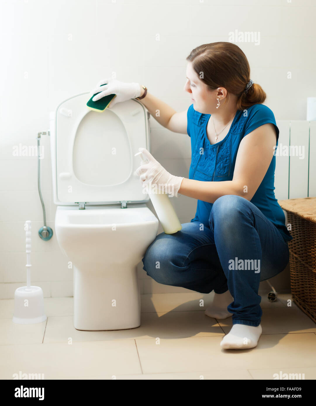 Girl Cleaning Toilet Seat With Sponge And Cleaner At Her Home Stock - Bathroom cleaning lady